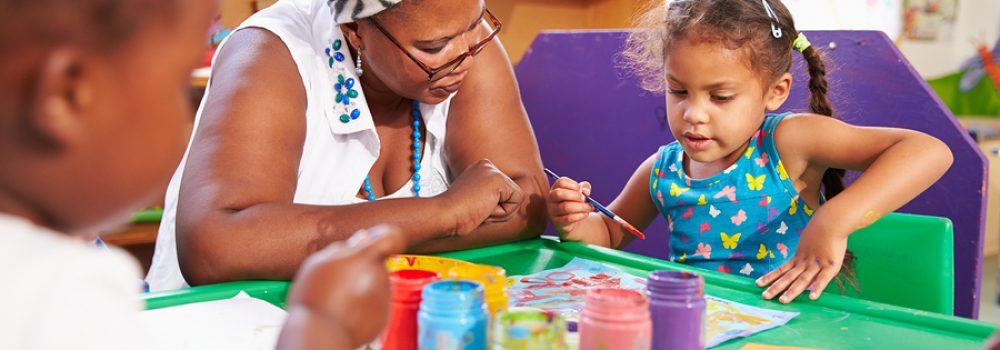 Teacher Sitting With Kids In A Preschool Class, Close Up